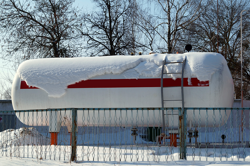 Fuel tank of liquid propane gas station. Fuel tank of LPG station under snow. Winter view of  LPG station for filling liquefied gas into the vehicle. Environmentally friendly fuel.