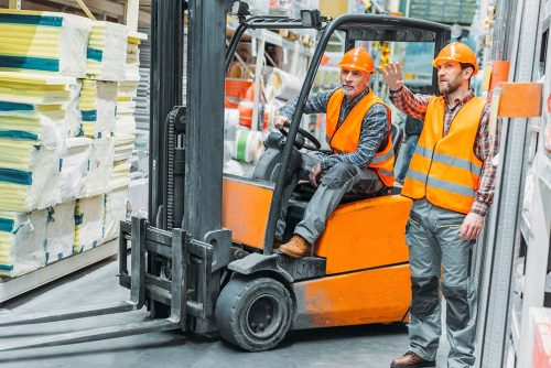 worker and his senior colleague working with forklift machine in storage